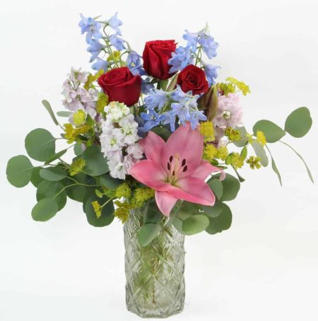 A pastel bouquet featuring pink Asiatic lilies, fragrant pink stock, light blue delphinium and accents in a clear glass vase.
